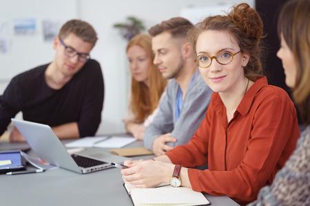Groep jonge mensen uit het bedrijfsleven in een teamvergadering zitten rond een tafel in het kantoor met focus naar een jonge vrouw op zoek naar de camera met een glimlach