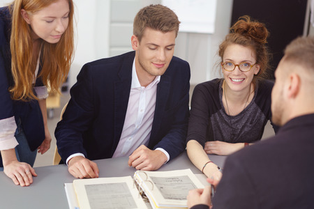 large office: Group of young businesspeople in a meeting sitting grouped around a large office binder of notes having a brainstorming session