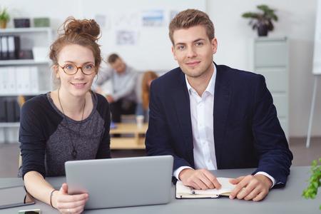 mujeres juntas: Dos joven cómoda de la oficina Compañeros de trabajo sentados trabajando juntos en un ordenador portátil mirando a la cámara con una sonrisa en un concepto de trabajo en equipo