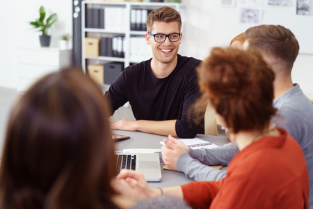 sit around: Handsome smiling businessman in a meeting with diverse co-workers as they sit around a table brainstorming together Stock Photo