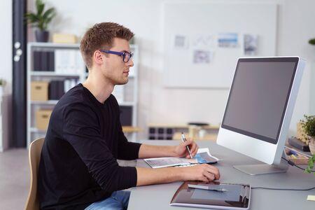 monitor de computadora: Joven empresario que usan gafas sentado en su escritorio en la oficina de trabajo en un gran monitor ordenador de sobremesa, vista lateral