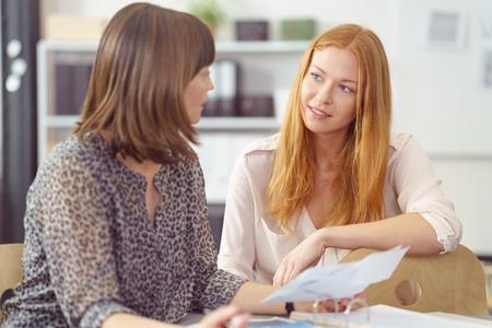 Deux femmes d'affaires dans une discussion sérieuse assis à un bureau ensemble regardant paperasse, se concentrer à une jeune rousse attrayante Banque d'images - 55666274