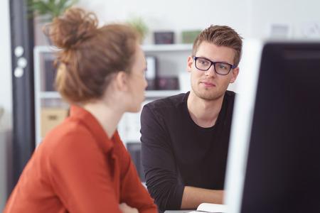 Ernstige jonge zakenman in een vergadering te luisteren naar een vrouwelijke collega met een nadenkende uitdrukking Stockfoto - 55666284