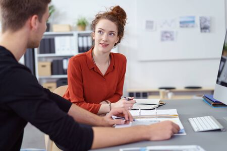 Attractive young businesswoman in a discussion with a male colleague listening to him as she sits at the desk with a journal taking notes