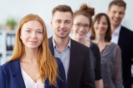 Empresaria joven atractiva que presenta con su equipo de compañeros de trabajo en una línea de retroceso detrás de ella mirando a la cámara con una sonrisa de confianza