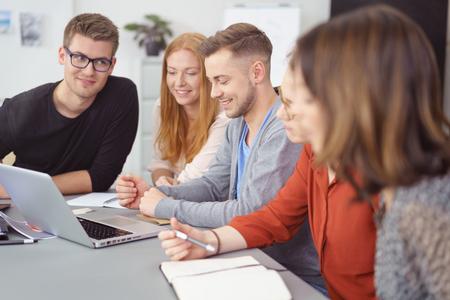 Groep van jonge ondernemers in een teamvergadering zitten samen rond een laptop op een tafel glimlachen als ze de gegevens te lezen op het scherm Stockfoto