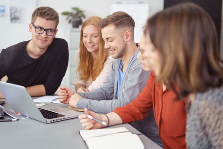 Group of young business entrepreneurs in a team meeting sitting together around a laptop on a table smiling as they read the data on the screen