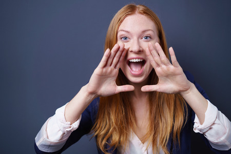 Excited pretty young redhead woman yelling at the camera with her hands cupping her mouth to magnify her voice, dark studio background