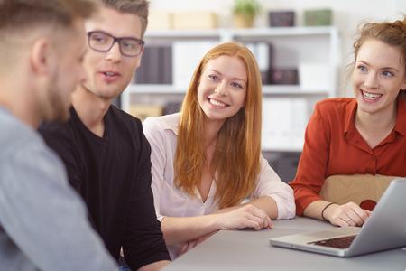 Glimlachende jonge vrouw in een zakelijke bijeenkomst met twee mannelijke en een vrouwelijke collega kijken naar de mannen met een geïnteresseerde uitdrukking als ze praten