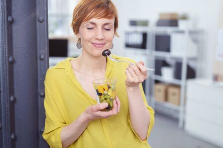 eating salad: Cute red haired woman snacking on fruit from clear plastic cup in small office with eyes closed and grinning Stock Photo