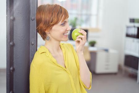 Vue profil sur jolie jeune femme aux cheveux roux en blouse jaune debout près du poteau dans le petit bureau de manger une pomme verte Banque d'images - 57000620