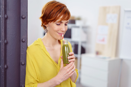 Waist Up Portrait of Woman with Short Red Hair Wearing Bright Yellow Blouse Sipping Healthy Green Bottled Shake from Straw While Standing in Bright Modern Home Office with Eyes Closed in Bliss