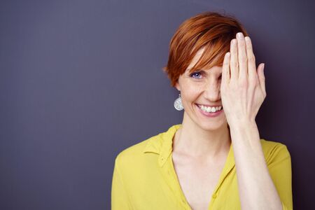 hand covering eye: Happy young woman covering one eye with her hand as she grins at the camera, head and shoulders on a dark background with copy space