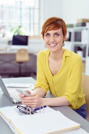 yellow shirt: Single cheerful red haired business woman in yellow shirt sitting at desk with three ringer binder, eyeglasses, phone and laptop computer Stock Photo