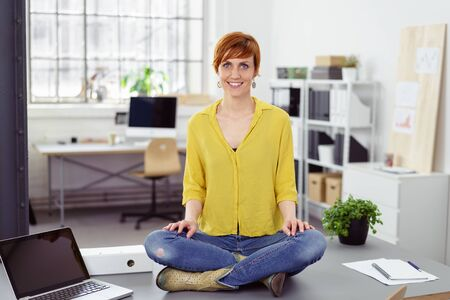 workplace wellness: Full Length Portrait of Young Smiling Businesswoman with Short Red Hair Wearing Bright Yellow Blouse, Blue Jeans and Boots Sitting Cross Legged on Desk in Bright Home Office Stock Photo