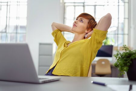 deep thought: Single calm young office worker in yellow shirt and red hair with hands behind head looking upward in deep thought with laptop computer in foreground