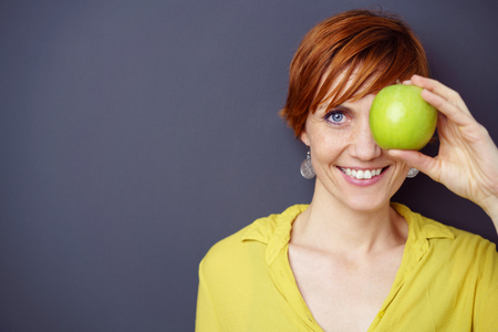 gray eyes: Happy smiling young redhead woman covering her one eye with a fresh green apple while looking at the camera with a lovely friendly smile, with copy space Stock Photo