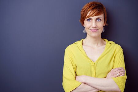 adult wall: Cute single adult red haired grinning female standing near blank dark wall with folded arms Stock Photo