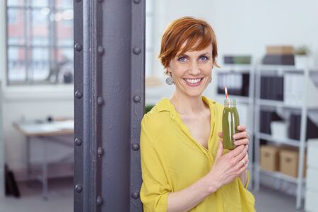 happy work: Happy smiling woman in yellow blouse taking a break from work at her office to drink from a tall glass bottle of healthy green vegetable smoothie