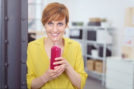 grins: Healthy young woman enjoying a berry smoothie during her lunch break at the office drinking it from a glass bottle as she grins at the camera