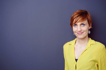 adult wall: Cute single adult blue eyed red haired grinning female wearing yellow blouse standing near blank dark wall