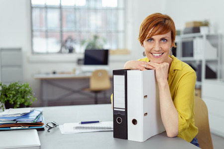 Smiling red haired female business person in yellow shirt sitting at desk using cell phone beside with three ringer binder, eyeglasses and laptop computer