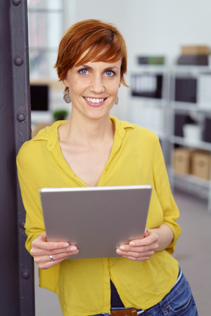 Cute single young red haired woman in yellow blouse with cheerful expression standing beside iron column holding tablet computer in small office photo