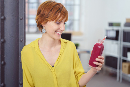 Happy red haired woman taking a break from work in her office to look at a blank fruit drink bottle with straw photo