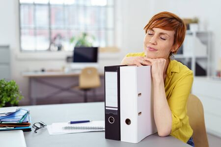Woman with grin and closed eyes relaxing head on hands over pair of notebook binders in small office photo