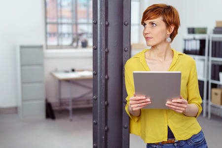Single young female small business owner holding tablet computer and leaning against iron column looking over toward area with copy space photo