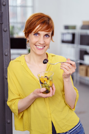 Cute red haired woman snacking on fruit from clear plastic cup at work with small office scene behind her photo