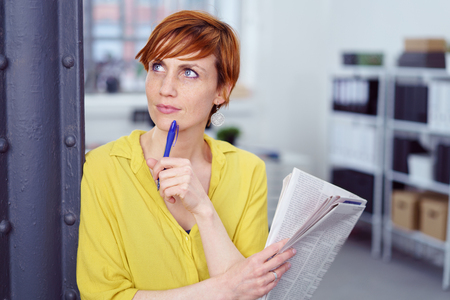 Waist Up Portrait of Woman with Short Red Hair Leaning Against Pole in Modern Home Office Holding Pen and Newspaper and Looking Deep in Thought - Doing Crossword or Reading Ads Stock Photo