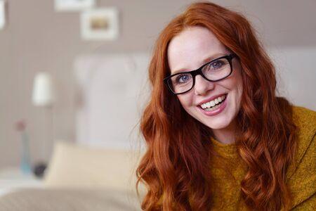Enig leuk lachend rood geleid wijfje in oogglazen en gele sweaterzitting op bed die naast exemplaarruimte lachen