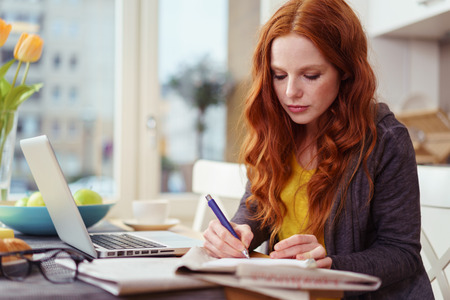 Serious beautiful young adult woman with red hair taking notes while sitting in front of laptop computer on kitchen table near window
