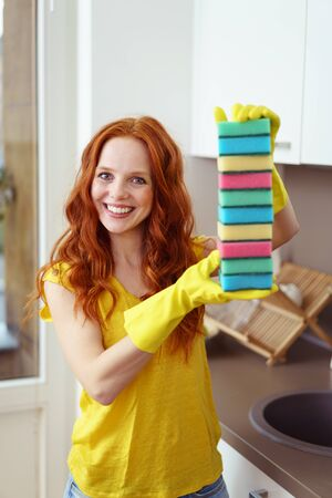 scrubbing: Single beautiful cleaning woman in long red hair, yellow shirt and rubber gloves proudly showing off colorful scrubbing sponges