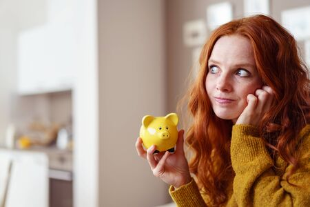 Frustrated single woman in red hair and yellow sweater holding a little yellow piggy bank while looking away Stock Photo