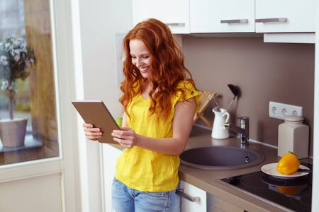 long red hair: Single beautiful young female with long red hair looking at her tablet computer while leaning against kitchen sink counter