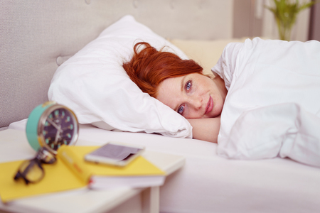 soulful: Pretty young woman lying in bed looking at the camera with soulful eyes as she pretends not to have heard her alarm clock