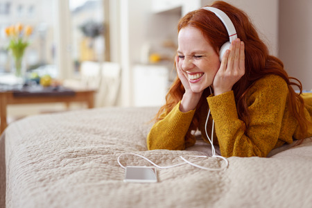 Happy single young woman in yellow sweater laying down on bed with eyes closed while listening to something enjoyable