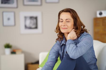 Mujer tensionada tomar un momento para relajarse sentado en un sofá en casa con su mano a su cuello y los ojos cerrados con una expresión serena