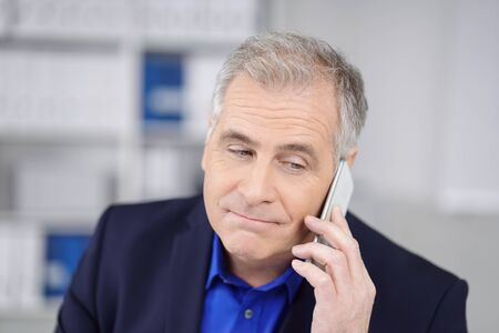 phone calls: Dubious businessman listening to a phone call on his mobile with a wry grimace and sidelong glance, close up head and shoulders