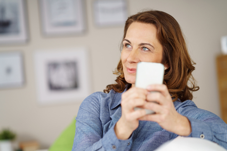 Single beautiful mature cheerful adult woman in blue blouse and brown hair looking away while holding smart phone