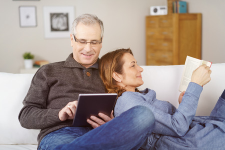 he she: Happy middle-aged married couple relaxing together at home with the wife lying back against her husband as she reads a book while he surfs the internet on a tablet Stock Photo