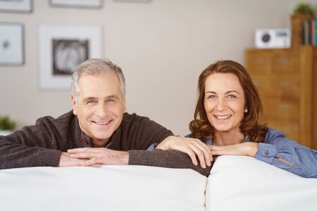 crouched: Smiling middle aged couple crouched behind white couch near chest of drawers with framed photos on the wall Stock Photo