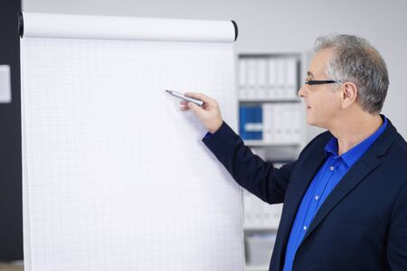 gray haired: Single gray haired businessman in blue blazer and shirt pointing at large blank grid chart with pen in office