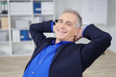 detras de: empresario confía relajado con una amplia sonrisa se sienta de nuevo en su silla en la oficina con las manos entrelazadas detrás de la cabeza