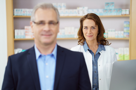 drug store: Business man at drug store standing at counter near female pharmacist besides shelf filled with medicine