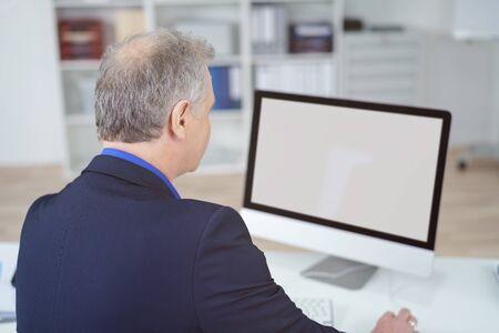 monitor de computadora: Un empresario que trabaja un monitor de ordenador de pantalla grande de ancho, con una pantalla en blanco mientras se sienta en su escritorio con es nuevo a la cámara Foto de archivo