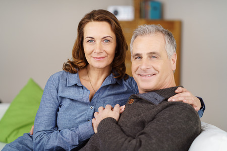 Attractive middle aged male and female couple holding hands together on sofa next to green pillow in living room