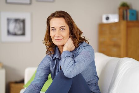 Beautiful grinning mature woman with confident expression holding hand behind neck while sitting on white sofa in living room